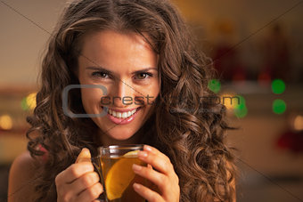Portrait of happy young woman with cup of ginger tea