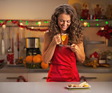 Happy young woman drinking ginger tea in christmas decorated kit