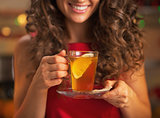 Closeup on happy young woman with cup of ginger tea