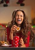 Happy young woman enjoying christmas snacks in kitchen