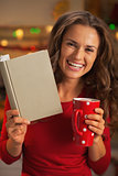 Happy young woman with book cup of hot chocolate