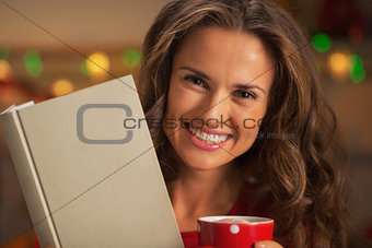 Portrait of happy young woman with book cup of hot chocolate