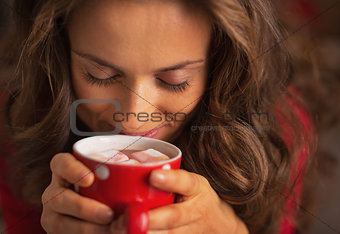 Portrait of happy young woman enjoying cup of hot chocolate with