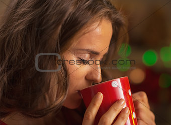 Portrait of young woman enjoying cup of hot chocolate