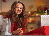 Happy young woman with shopping bags in christmas decorated kitc