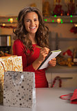 Happy young woman with shopping bags checking list of gifts in c