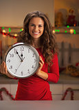 Portrait of smiling young woman holding clock in christmas decor