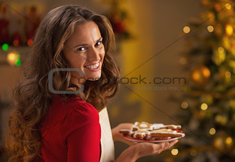 Portrait of smiling young housewife with plate of christmas cook