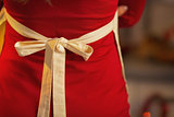 Closeup on young housewife in red dress wearing apron. rear view