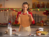 Happy young housewife showing dough in christmas decorated kitch