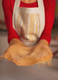 Closeup on smiling young housewife with dough