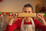 Young housewife holding rolling pin in front of face