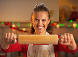 Smiling young housewife showing rolling pin