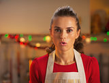 Portrait of surprised young housewife in christmas decorated kit