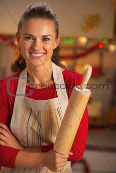 Portrait of smiling young housewife with rolling pin