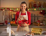 Happy young housewife whisking dough in christmas decorated kitc