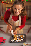 Smiling young housewife decorating christmas cookies in kitchen