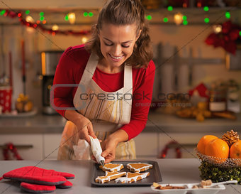Happy young housewife decorating christmas cookies in kitchen