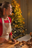 Happy young woman chopping walnuts in christmas decorated kitche