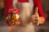 Closeup on young housewife showing jar with honey nuts and thumb