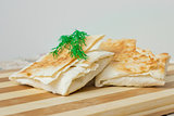 Envelopes of pita with dill on a wooden board