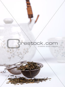 Pot of tea with fresh tea over a white background