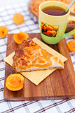 Piece of apricot tart on the wooden board with cup of tea
