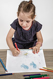 Cute Little Girl Painting on a School Desk
