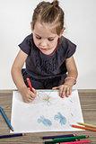 Cute Little Girl Painting on a School Desk