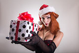 Pretty redhead pin-up girl in Santa Claus hat holding gift box