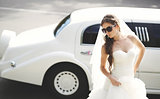 Young bride against limo. Hot summer day.