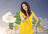 Composite image of smiling curly haired pretty woman changing channel with remote