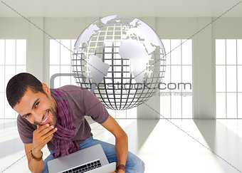 Composite image of thoughtful man sitting on floor using laptop and smiling at camera