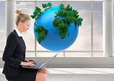 Composite image of businesswoman using laptop