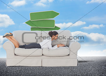 Composite image of business woman lying on couch