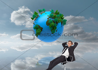 Composite image of manager relaxing in office with team in background