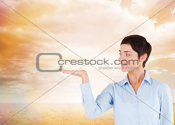 Composite image of businesswoman with an open hand to show a copy space