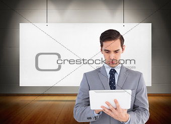 Composite image of businessman holding a tablet computer