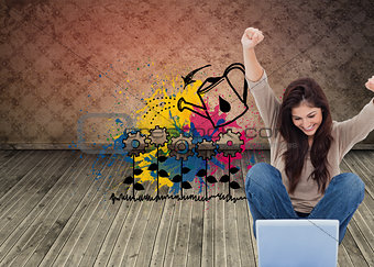Composite image of brunette cheering while using laptop