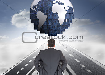 Composite image of businessman standing back to the camera with hands on hip