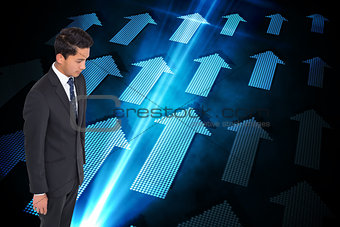 Composite image of stern businessman looking down