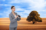 Composite image of curious young businesswoman with binoculars