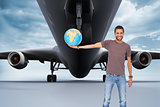Composite image of handsome man holding out a globe