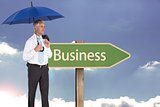 Composite image of happy businessman holding umbrella