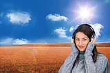 Composite image of beautiful model wearing winter clothes listening to music