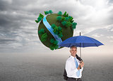 Composite image of businessman holding umbrella smiling at camera