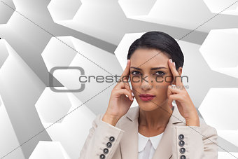 Composite image of young businesswoman putting her fingers on her temples
