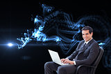 Composite image of young businessman sitting on an armchair working with a laptop