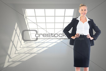 Composite image of businesswoman standing with hands on hips