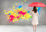 Composite image of businesswoman standing back to camera holding red umbrella
